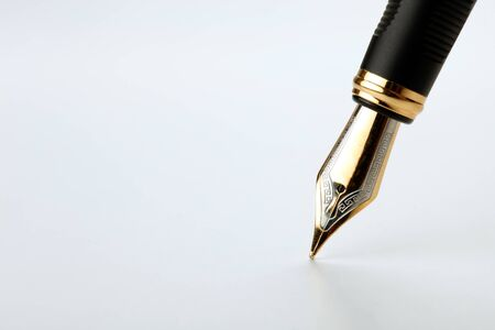 Stylo plume d'or écrit sur un fond blanc libre