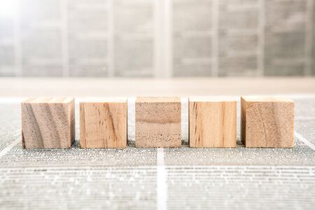 Five wooden cube blocks on a newspaper background closeup