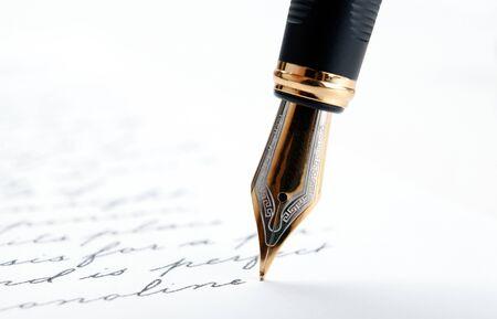 Pluma estilográfica sobre papel con texto de tinta sobre un fondo blanco closeup Foto de archivo