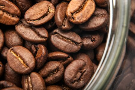 roasted coffee beans in a glass jar close up