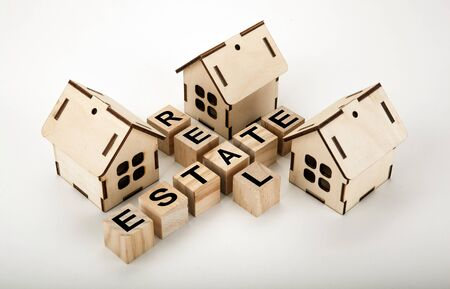 Cubes with inscription real estate in the form of a crossword puzzle with three miniature houses