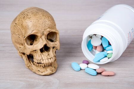 colored medical pills and a jar and a miniature human skull