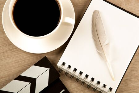 movie clapper, cup of coffee and fountain pen diary