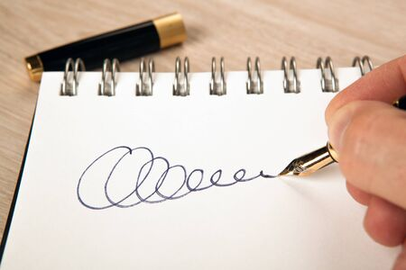 golden fountain pen in the hand and a signature on the paper close up
