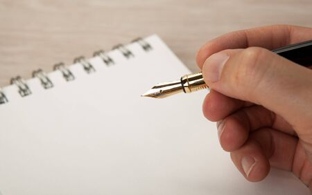golden fountain pen in the hand and a diary close up Stock fotó