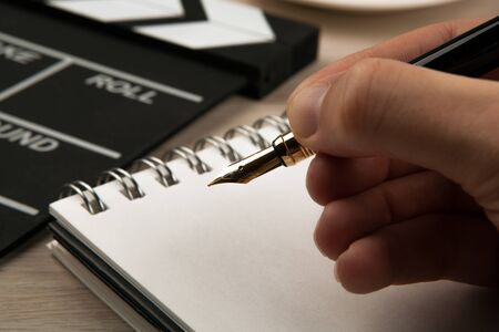fountain pen in the hands of a screenwriter on the background of a movie clapper and a notebook