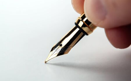 fountain pen in the hand on the white paper closeup