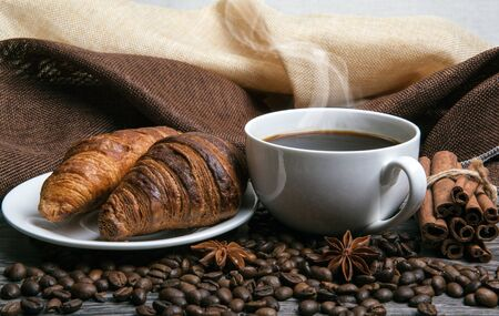 cup of hot coffee and roasted coffee beans with toasted croissants closeup
