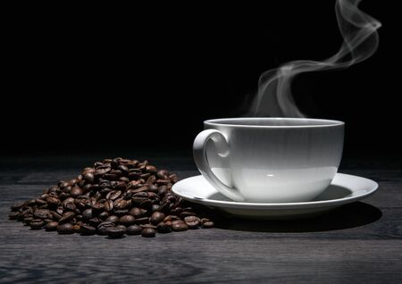 cup of hot coffee and roasted coffee beans on a wooden table