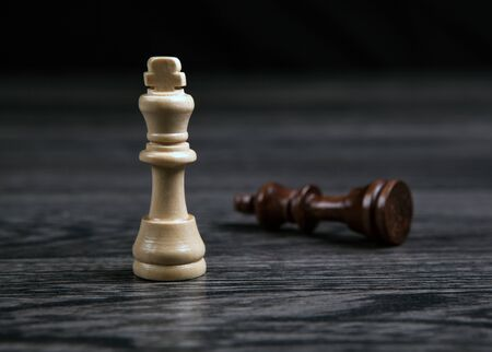 the white king defeats the black king in chess on a wooden table closeup Фото со стока