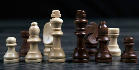 chess kings and various chess pieces arranged in a row on a wooden background as a still life Фото со стока