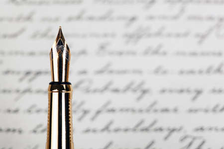 golden fountain pen with ink text background closeup