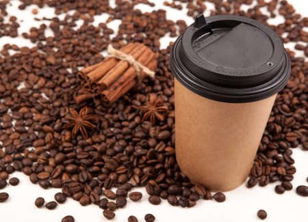 cardboard cup of black coffee with roasted coffee beans and anise, cinnamon
