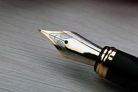 gold plated fountain pen closeup on the table