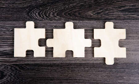 Three puzzle pieces in a row on a wooden background top view