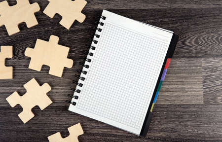 notepad with puzzle pieces on a wooden background top view