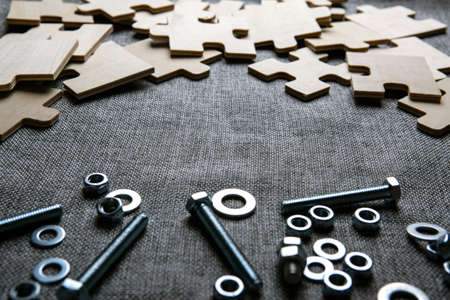 puzzle elements and and steel nuts, bolts on a textile background closeup