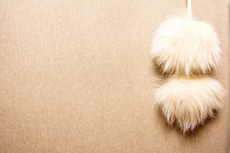 cashmere beige background with two blonde fur pompons
