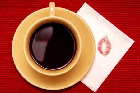 Cup of coffee (tea, chocolate) and napkin with kiss over red mat