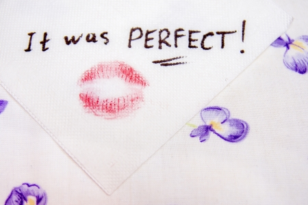 Note on napkin with lipstick kiss over the bed-clothes Stock Photo