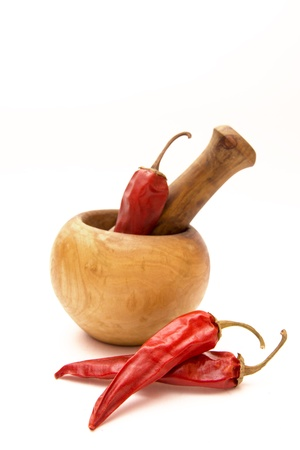 Dried red hot peppers with wooden mortar and pestle isolated on white. Selective focus. photo