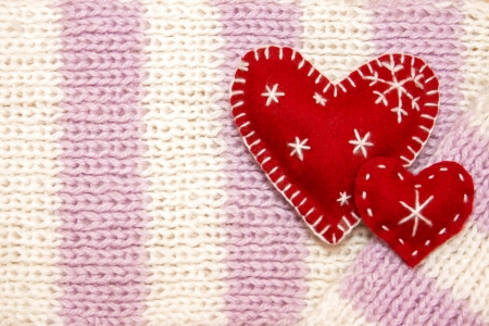Christmas concept. Knitted wool jersey texture with two red handmade hearts photo