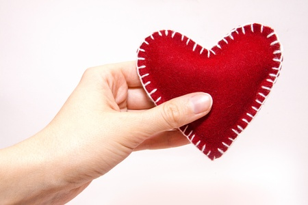 Womans hand holding a heart isolated on white background