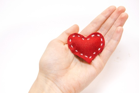 cordiality: Womans hand holding a heart isolated on white background