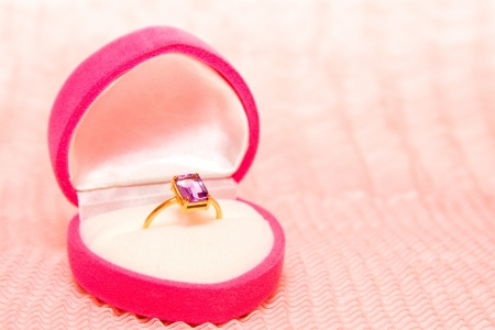 Golden ring with amethyst in pink heart shaped box on pink chiffon texture photo