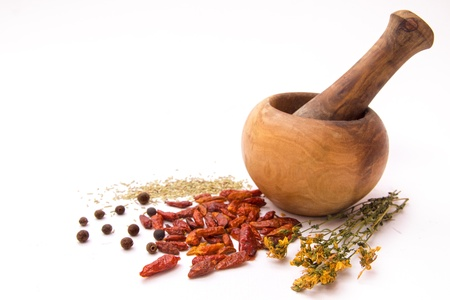 Hot spices with wooden mortar and pestle isolated on white background photo
