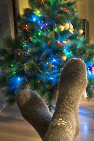 Winter evening. Feet in warm woolen socks around the Christmas tree. Stock Photo - 17588085