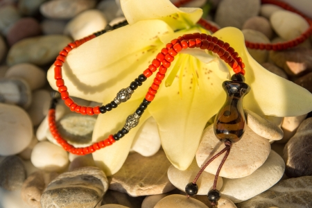 handmade jewelry with yellow lily on sea pebbles, sunlight Stock Photo - 17588093