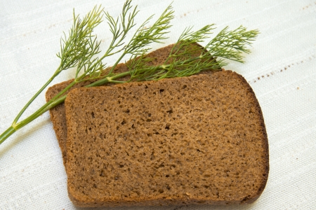 heathy diet: Bread  and dill over linen tablecloth.