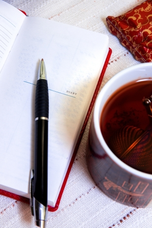 detai: Dairy book, pen and cup of tea. Morning planning at breakfast.