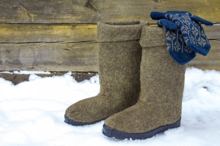 impoverished: Russian winter concept. Boots (valenki) and mittens over wooden and snow background. Stock Photo