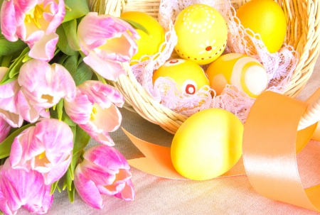 Easter concept  Basket painted Easter eggs and pink tulips over linen background  photo