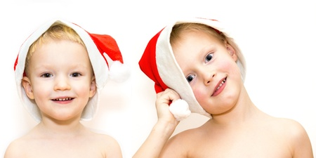 Two children in Santa hats isolated on white background photo