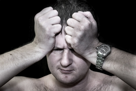 Dark portrait of a man holding his head in despair photo