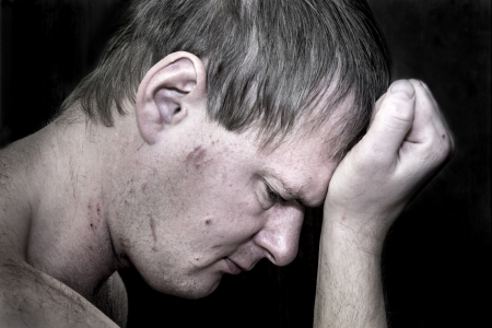 Dark portrait of a man holding his head in despair Stock Photo - 17540222