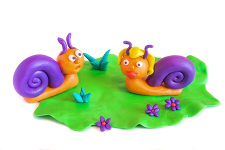 plasticine: Two funny snails on grass, clay (plasticine) modeling isolated on white background.