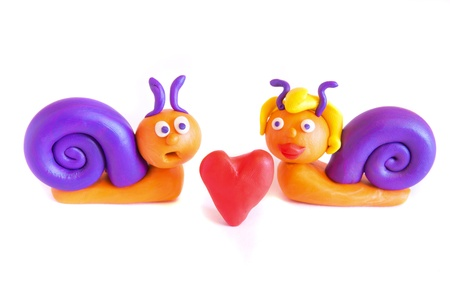 modeling: Two funny snails in love, clay (plasticine) modeling isolated on white background.