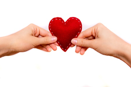 Female hand holding red heart isolated on white. Love and valentine concept.