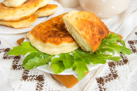 pasty: Fried patties with curd cheese and arugula garnish on tablecloth.