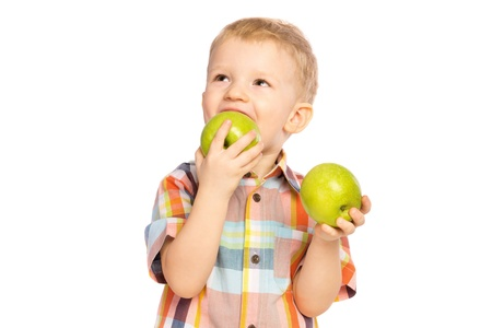 Beautiful happy smiling joyful child (little boy) eating healthy food (green apples) and looking up  isolated on white background photo