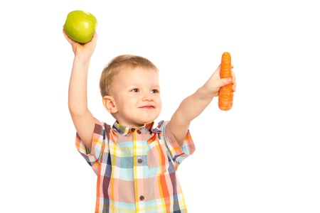 Beautiful happy smiling joyful child (little boy) eating healthy food (green apples, carrot) and looking up  isolated on white background
