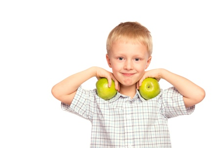 Beautiful happy smiling joyful child (little boy) eating healthy food (green apples)   isolated on white background photo