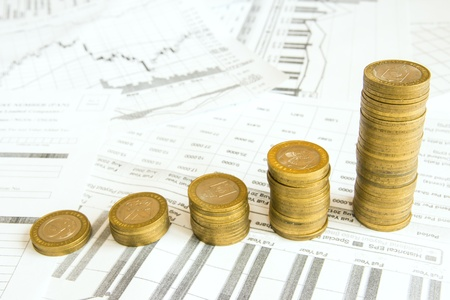 Stacks of gold coins like increasing columns over different paper documents background. Earnings or saving graph (diagram).
