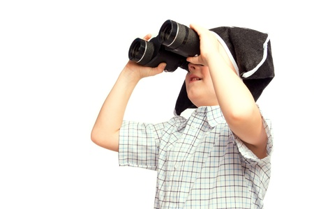 Beautiful happy child (little boy) in pirate hat looking in binoculars isolated on white background. Search or adventure concept. photo
