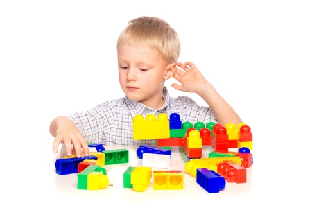 Beautiful happy smiling joyful child (little boy) playing and  building plastic construction (educational game)  isolated on white background. photo
