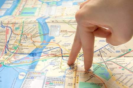 Female fingers (hand) walking on map of New York City. Travel concept. photo